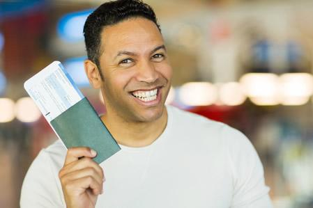 depositphotos 51625535 Man holding passport and boarding pass